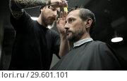 Купить «Haircut of dark haired bearded man in barbershop», видеоролик № 29601101, снято 19 декабря 2018 г. (c) Andriy Bezuglov / Фотобанк Лори