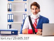 Купить «The injured employee working in the office», фото № 29605337, снято 20 сентября 2018 г. (c) Elnur / Фотобанк Лори