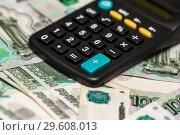 Карманный калькулятор и много тысячных купюр. Стоковое фото, фотограф Игорь Низов / Фотобанк Лори