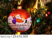 Купить «Новогодний шарик с изображением Деда Мороза едущего на санях висит на ёлке», эксклюзивное фото № 29616909, снято 25 декабря 2018 г. (c) Игорь Низов / Фотобанк Лори