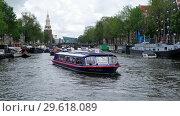 Купить «Oudeschans (Nouveau canal) in Amsterdam with passenger ships on foreground and Keizersbrug bridge, Montelbaanstoren Tower with NEMO Science Museum on background», видеоролик № 29618089, снято 29 апреля 2018 г. (c) Serg Zastavkin / Фотобанк Лори