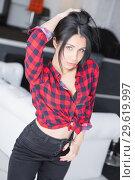 Купить «Attractive young woman posing near a white sofa.», фото № 29619997, снято 8 января 2016 г. (c) Сергей Сухоруков / Фотобанк Лори