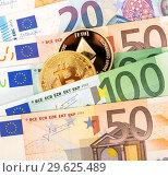 Купить «Cryptocurrency coins lying on the euro banknotes», фото № 29625489, снято 20 января 2018 г. (c) FotograFF / Фотобанк Лори