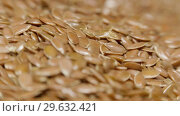 Rain of flax seeds on rotating table, macro view, healthy food. Стоковое видео, видеограф Dzmitry Astapkovich / Фотобанк Лори