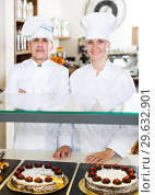Купить «Experienced man and woman staff offering cakes», фото № 29632901, снято 22 апреля 2017 г. (c) Яков Филимонов / Фотобанк Лори