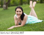 Купить «portrait of smiling young girl while lying in outdoors», фото № 29632997, снято 18 апреля 2017 г. (c) Яков Филимонов / Фотобанк Лори