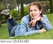 Купить «portrait of young female while lying in spring green garden», фото № 29633081, снято 18 апреля 2017 г. (c) Яков Филимонов / Фотобанк Лори