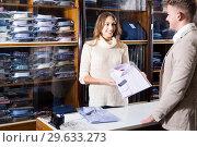 Купить «Female shopping assistant offering various shirts in men's cloths store», фото № 29633273, снято 26 марта 2019 г. (c) Яков Филимонов / Фотобанк Лори