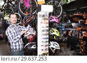 Купить «Man demonstrates helmets for cycling», фото № 29637253, снято 23 января 2019 г. (c) Яков Филимонов / Фотобанк Лори