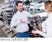 Купить «Salesman helps to choose the saucepans», фото № 29637281, снято 8 февраля 2017 г. (c) Яков Филимонов / Фотобанк Лори