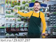Купить «Handsome seller demonstrating assortment», фото № 29637297, снято 2 марта 2017 г. (c) Яков Филимонов / Фотобанк Лори