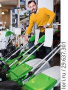 Купить «interested guy deciding on best lawnmower in garden equipment shop», фото № 29637301, снято 2 марта 2017 г. (c) Яков Филимонов / Фотобанк Лори