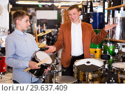 Купить «Boy and father choosing best drum», фото № 29637409, снято 29 марта 2017 г. (c) Яков Филимонов / Фотобанк Лори