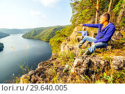 Купить «A tourist admires the picturesque view from above on the Yumaguzinsky reservoir on the Belaya River. Bashkortostan.», фото № 29640005, снято 31 августа 2018 г. (c) Акиньшин Владимир / Фотобанк Лори