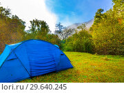 Купить «The tourist tent stands on a clearing in the autumn forest near the cliff.», фото № 29640245, снято 4 сентября 2018 г. (c) Акиньшин Владимир / Фотобанк Лори