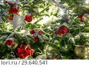 Купить «Fragment of a beautiful Christmas tree with ornaments and garlands in street in Moscow, Russia», фото № 29640541, снято 2 января 2019 г. (c) Володина Ольга / Фотобанк Лори