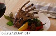 Купить «Young lamb ribs served with vegetables and herbs on plate», видеоролик № 29641017, снято 28 августа 2018 г. (c) Яков Филимонов / Фотобанк Лори