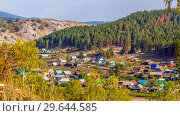 Купить «Panoramic scenic view from above of the Ural village on the banks of the river among the mountain peaks and taiga. The nature of the Urals.», фото № 29644585, снято 7 сентября 2018 г. (c) Акиньшин Владимир / Фотобанк Лори