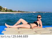 Купить «Улыбающаяся девушка загорает у моря на понтоне», фото № 29644689, снято 23 апреля 2019 г. (c) Светлана Кузнецова / Фотобанк Лори