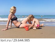 Купить «Mom and little daughter playing with sand on the beach by the sea», фото № 29644985, снято 19 июля 2019 г. (c) Светлана Кузнецова / Фотобанк Лори
