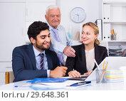 Купить «Employees are demonstrating reports on laptop to mature boss», фото № 29648361, снято 27 июня 2017 г. (c) Яков Филимонов / Фотобанк Лори