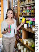 Купить «Portrait of young woman choosing candles», фото № 29648621, снято 18 апреля 2019 г. (c) Яков Филимонов / Фотобанк Лори