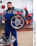 Купить «Adult is working at restoring wheel», фото № 29658677, снято 19 января 2019 г. (c) Яков Филимонов / Фотобанк Лори