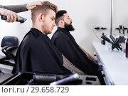 Купить «Young clients having their hair cut by hairdressers», фото № 29658729, снято 27 января 2017 г. (c) Яков Филимонов / Фотобанк Лори