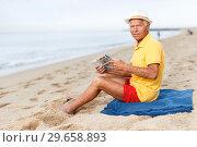 Купить «Nice mature man sitting and looking at booklet», фото № 29658893, снято 16 июня 2018 г. (c) Яков Филимонов / Фотобанк Лори