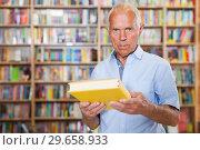 Купить «Portrait of serious intelligent older man in library with book in hands», фото № 29658933, снято 11 июня 2018 г. (c) Яков Филимонов / Фотобанк Лори