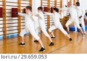 Купить «Group practicing fencing techniques in gym», фото № 29659053, снято 30 мая 2018 г. (c) Яков Филимонов / Фотобанк Лори