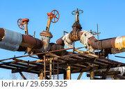 Купить «Old rusty pipeline with valves against the blue sky background», фото № 29659325, снято 10 февраля 2018 г. (c) FotograFF / Фотобанк Лори