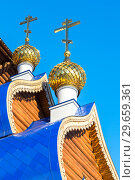 Купить «Golden domes with crosses on wooden orthodox church against the blue sky in Samara, Russia», фото № 29659361, снято 19 января 2018 г. (c) FotograFF / Фотобанк Лори