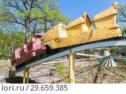 Купить «Old rusty carousel in a summer public park», фото № 29659385, снято 8 мая 2017 г. (c) FotograFF / Фотобанк Лори