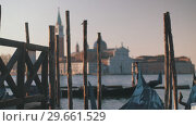 Купить «Gondolas moored at wooden piles. View with San Giorgio Maggiore Church, Venice», видеоролик № 29661529, снято 24 января 2019 г. (c) Данил Руденко / Фотобанк Лори