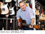 Купить «Male is playing on electric guitar», фото № 29662313, снято 18 сентября 2017 г. (c) Яков Филимонов / Фотобанк Лори