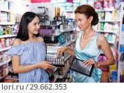 Купить «Stylish woman and daughter choosing eyeshadows in store», фото № 29662353, снято 21 июня 2018 г. (c) Яков Филимонов / Фотобанк Лори