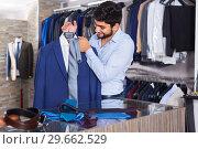 Купить «Man 25-33 years old is showing jacket and tie that he chose», фото № 29662529, снято 20 июня 2017 г. (c) Яков Филимонов / Фотобанк Лори