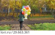 Купить «A slowmotion of a woman walking with balloons on a beautiful autumn day», видеоролик № 29663361, снято 21 февраля 2019 г. (c) Данил Руденко / Фотобанк Лори