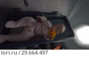 Купить «Baby girl in airplane bassinet», видеоролик № 29664497, снято 24 июня 2019 г. (c) Данил Руденко / Фотобанк Лори