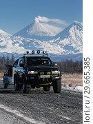 Купить «Японский внедорожник едет по автодороге на фоне вулканов», фото № 29665385, снято 7 января 2016 г. (c) А. А. Пирагис / Фотобанк Лори