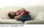 Купить «Attractive woman lying on Sofa», видеоролик № 29666197, снято 15 февраля 2008 г. (c) Wavebreak Media / Фотобанк Лори