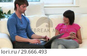 Couple Relaxing on Couch. Стоковое видео, агентство Wavebreak Media / Фотобанк Лори