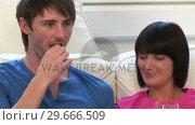 Купить «Young Couple Watching Television», видеоролик № 29666509, снято 1 марта 2008 г. (c) Wavebreak Media / Фотобанк Лори