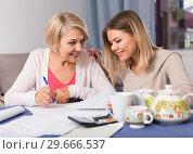 Купить «Daughter helps mother to lead home accounting», фото № 29666537, снято 13 ноября 2017 г. (c) Яков Филимонов / Фотобанк Лори