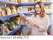 Купить «Positive woman buyer holding assortment of grocery food store», фото № 29666713, снято 11 апреля 2018 г. (c) Яков Филимонов / Фотобанк Лори
