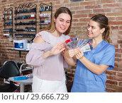 Купить «Positive woman client looking color of nail polish with manicurist», фото № 29666729, снято 30 мая 2018 г. (c) Яков Филимонов / Фотобанк Лори