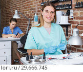 Купить «Female who doing manilure sitting at her workplace in nail salon», фото № 29666745, снято 30 мая 2018 г. (c) Яков Филимонов / Фотобанк Лори
