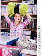 Купить «Woman choosing new coverlet», фото № 29666817, снято 20 марта 2019 г. (c) Яков Филимонов / Фотобанк Лори