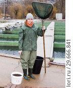Купить «Full-length portrait of female with landing net on fish farm», фото № 29666841, снято 4 февраля 2018 г. (c) Яков Филимонов / Фотобанк Лори